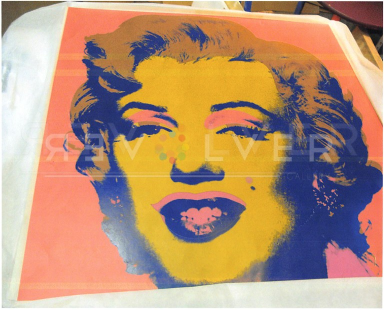 Andy Warhol Marilyn Monroe 27 screenprint out of frame laying on a table.