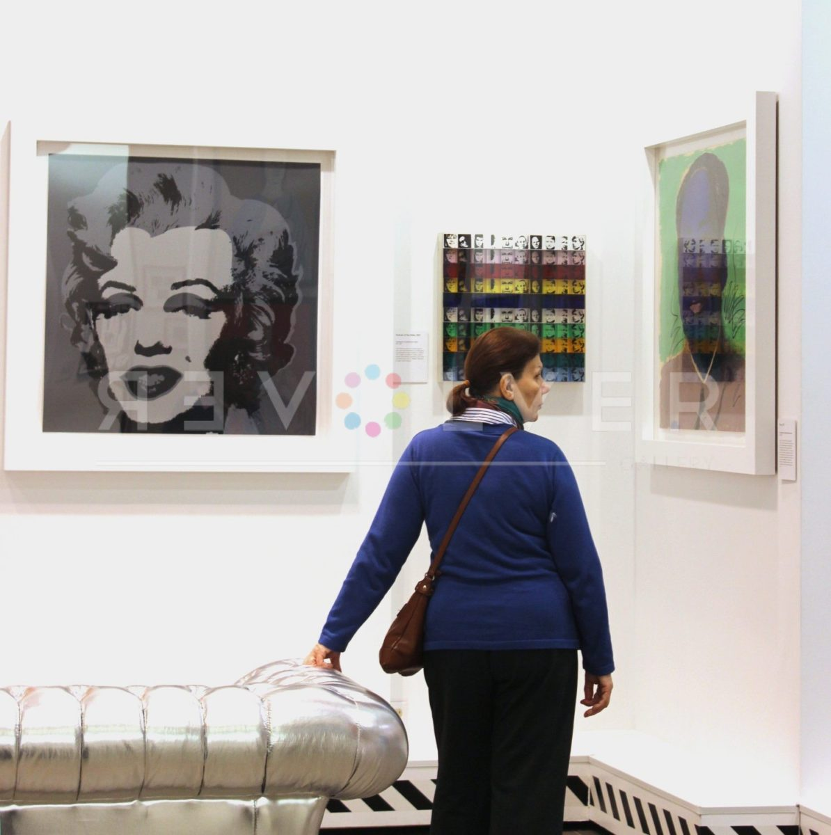 A Revolver Gallery patron viewing a Mao and Marilyn Monroe 24 screenprint.