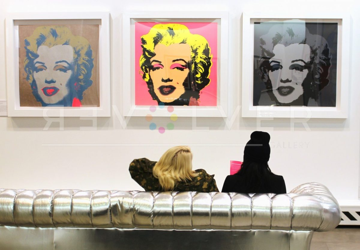 Two gallery visitors sit on a couch admiring Marilyn Monroe 24 by Andy Warhol and other Marilyn screenprints.