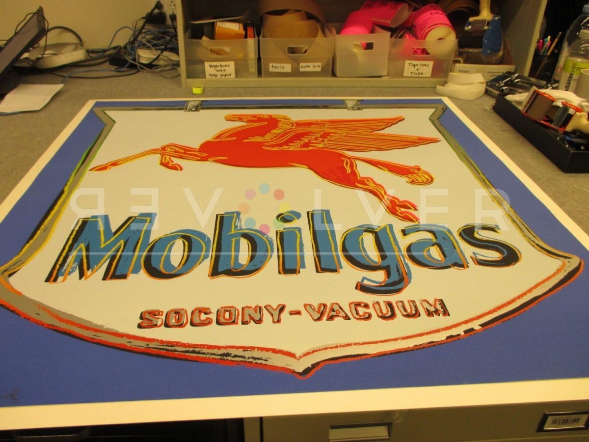 The Mobil 250 screenprint by Andy Warhol out of frame and laying on a table.