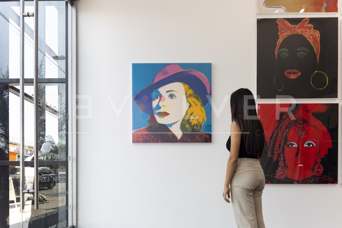 Gallery guest admiring the Ingrid Bergman With Hat 315 screenprint, showing the relative size of the artwork.