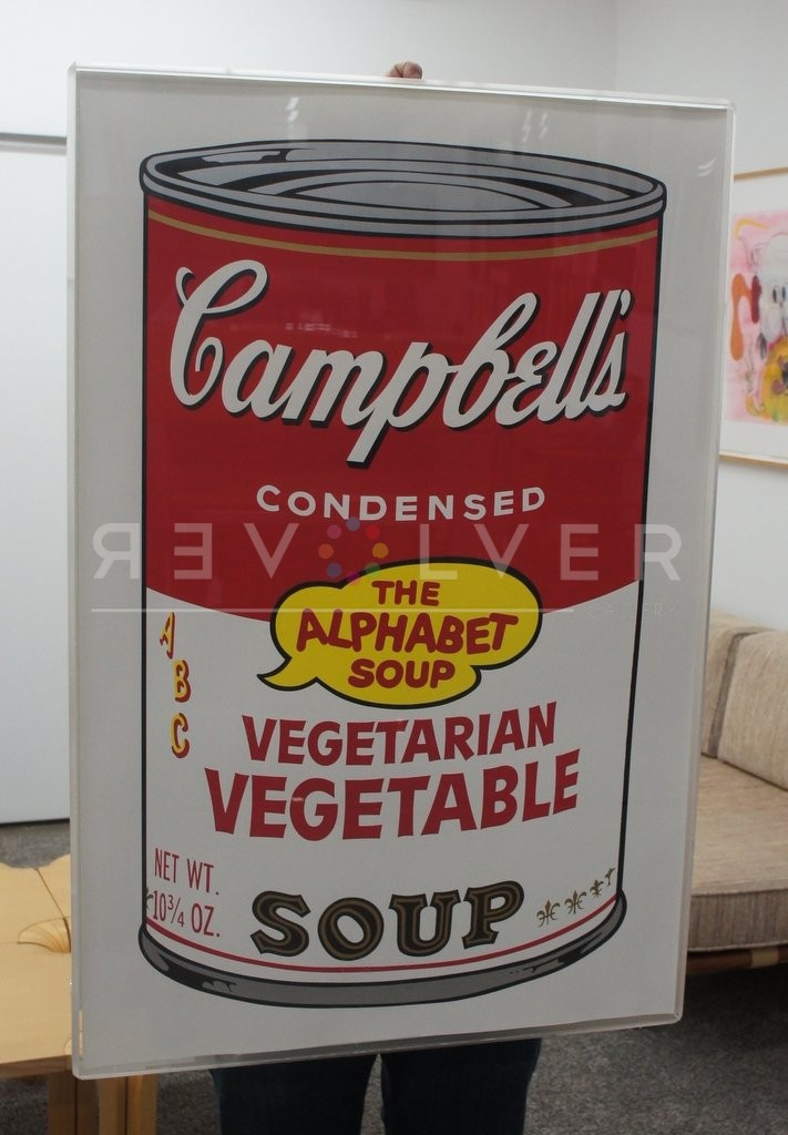Andy Warhol Campbell's Soup II: Vegetarian Vegetable 56 screenprint framed and being held by a person who is standing behind the print.