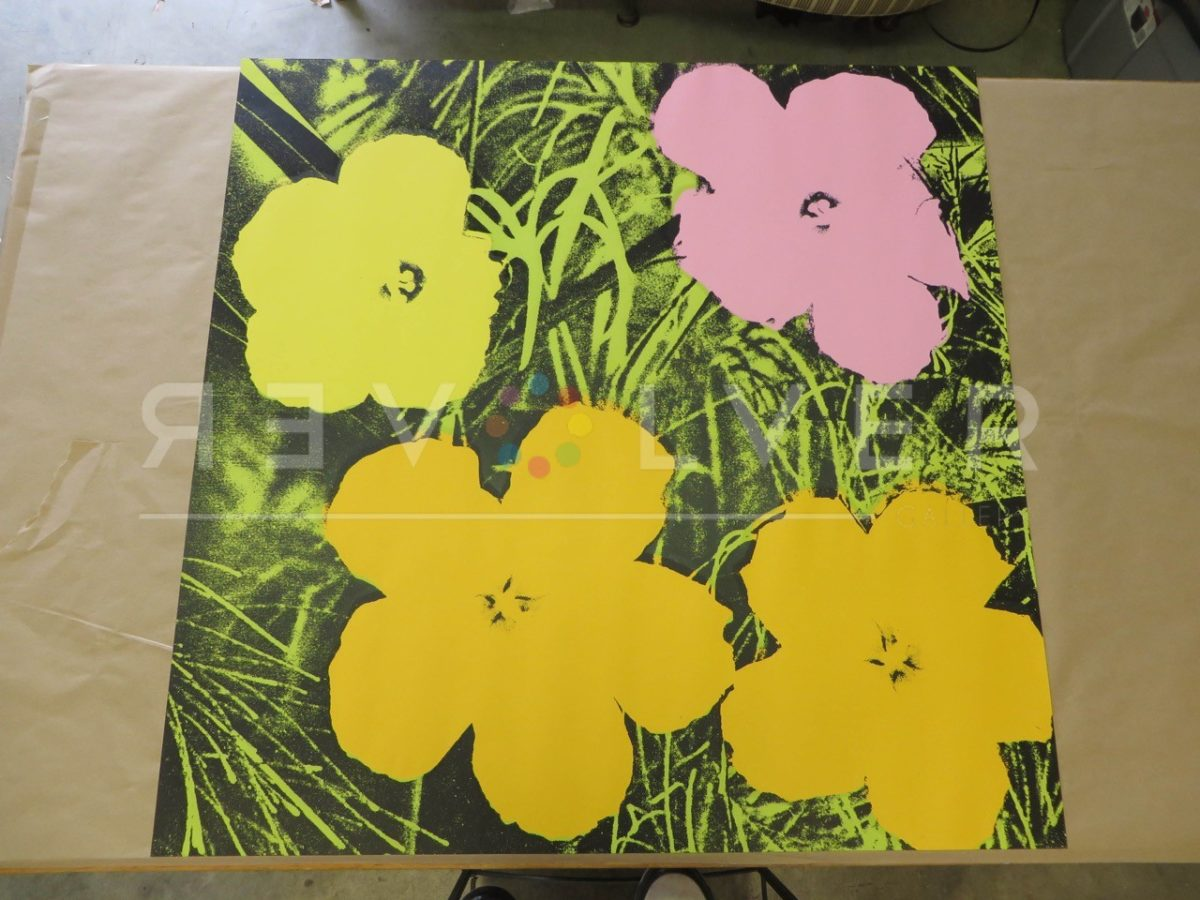 Andy Warhol Flowers 67 screenprint out of frame laying on a table.