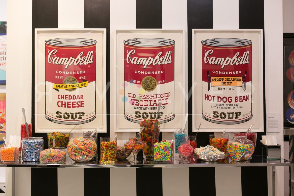 Campbell's Soup II: Cheddar Cheese 63 hanging on the wall next to Hot Dog Bean 59 and Old Fashioned Vegetable 54, above jars of candy.