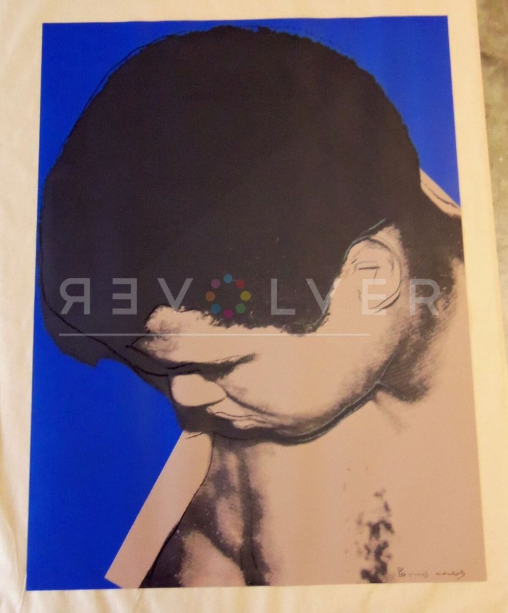 Shows the Muhammad Ali 180 screenprint by Andy Warhol out of frame laying on a table.