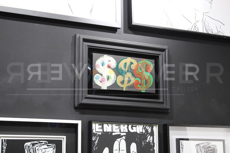 Andy Warhol Triple Dollar Sign in a black frame hanging on the gallery wall.