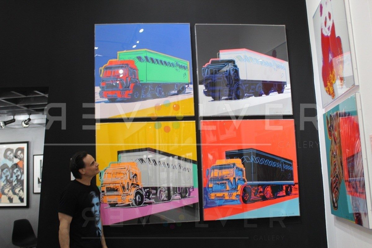 The complete truck portfolio by Andy Warhol hanging on the wall next to a gallery guest for size reference.