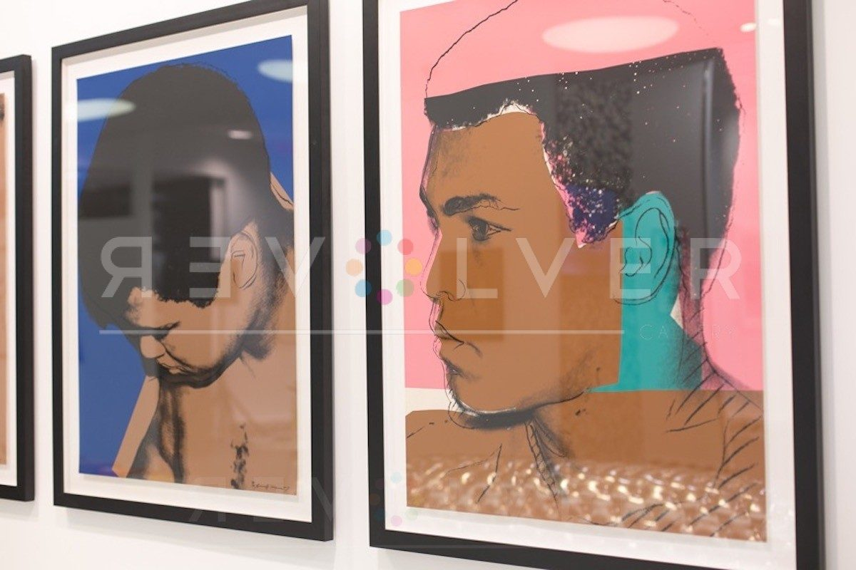 Shows Muhammad Ali 180 framed and hanging on the wall next to other muhammad Ali portraits.