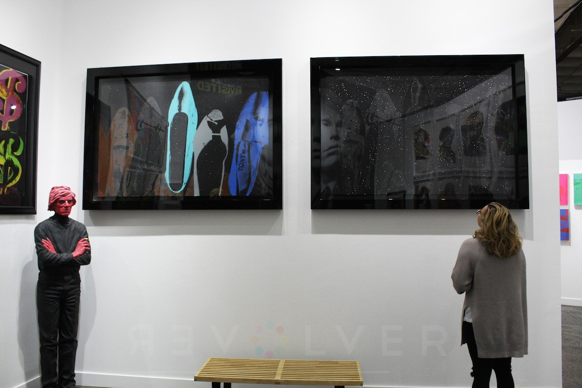 Gallery guest admiring two of the Shoes prints by Andy Warhol framed in black hanging on the wall.