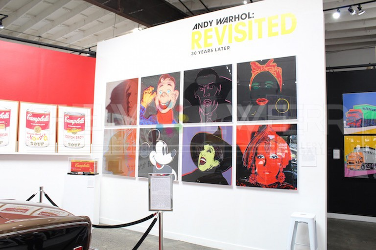 Photo of eight prints from Andy Warhol Myths hanging on the wall at Andy Warhol: Revisited exhibit.